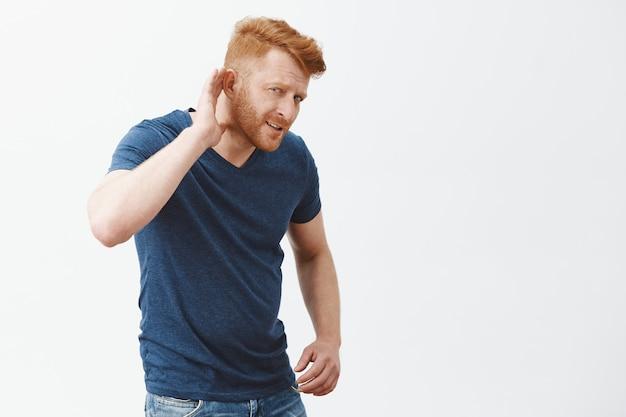 Dì cosa, ripeti, non puoi sentire. confusa bella rossa maschile con acconciatura alla moda e setole, tenendo la mano vicino all'orecchio, cercando di capire cosa dice l'uomo a voce alta