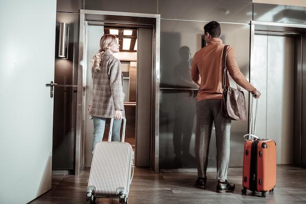 Прощай. светловолосая модная жена прощается с мужем, уезжающим в командировку