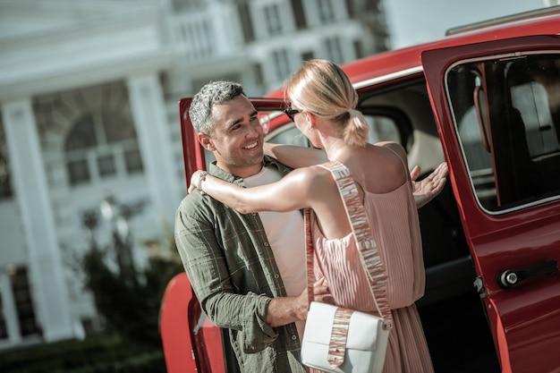 작별 인사. 웃고 있는 남자는 차 근처에 서서 떠나기 전에 아름다운 아내를 껴안고 있습니다.