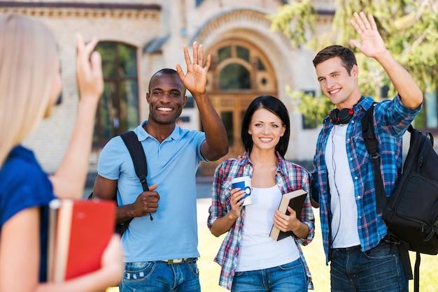友達に挨拶します。本を持って、屋外に立っている彼女の友人に手を振っている若い女性の背面図
