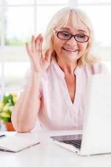 가장 가까운 그녀에게 인사합니다. 노트북을 보면서 손을 흔드는 쾌활한 시니어 여성