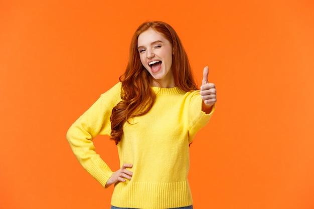 はいと言って。親指のアップのジェスチャーを与える黄色いセーターで陽気な赤毛の女性