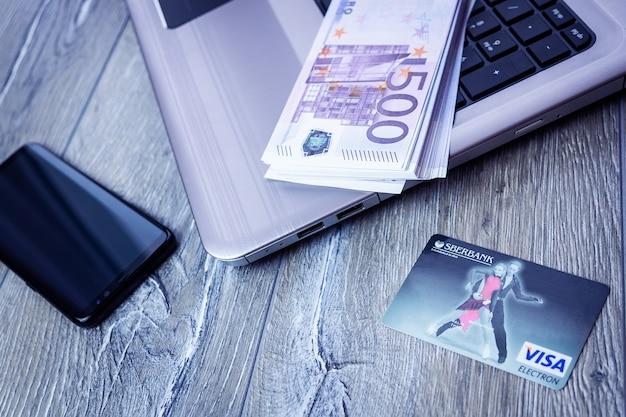 ラップトップとスマートフォンを備えたsberbank visaカード
