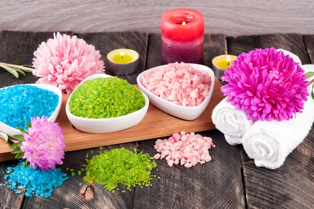 Sblue, green and pink sea salt, towel, scented candles and flowers for spa treatments on old wooden background