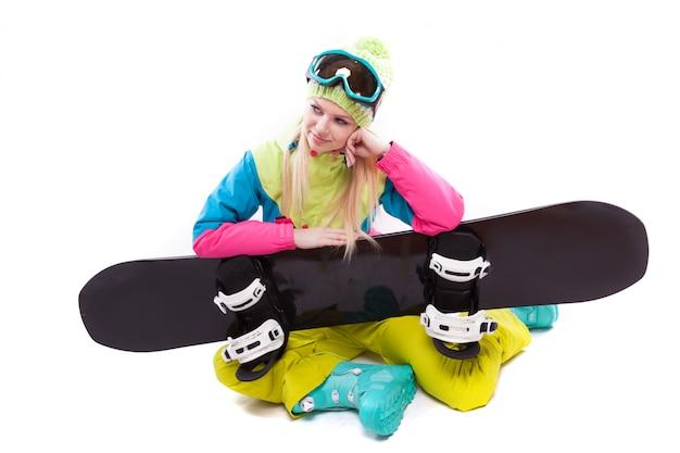 スキースーツとスキー用メガネの若い女性の美しさは、sbowboardで座る