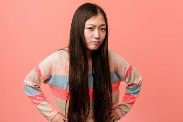 非常に怒っている誰かをscる若いクールな中国人女性。