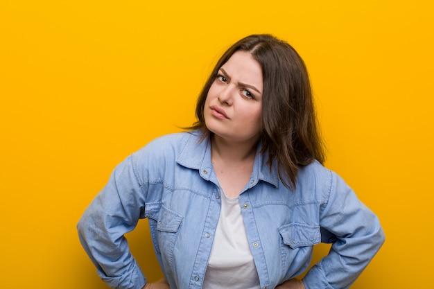 非常に怒っている誰かをscる若い曲線美プラスサイズの女性。