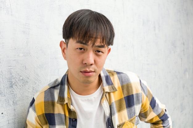 非常に怒っている誰かをscる若い中国人男性の顔のクローズアップ