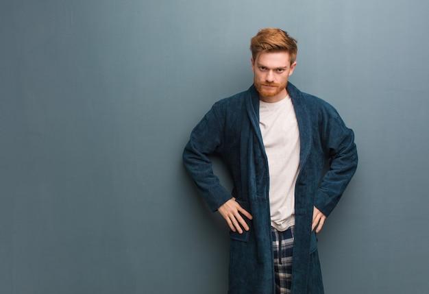 非常に怒っている誰かをscるパジャマで若い赤毛の男