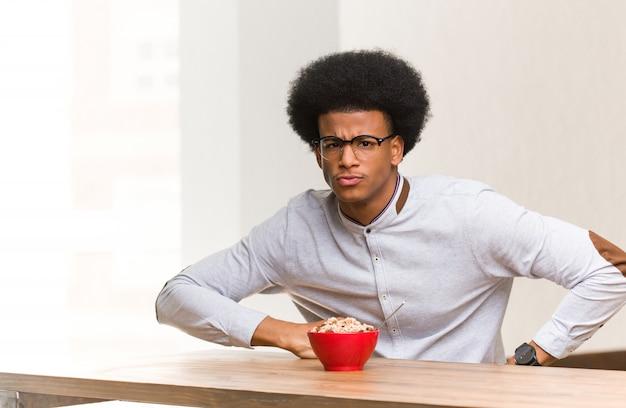 非常に怒っている誰かをscる朝食を持っている若い黒人男性
