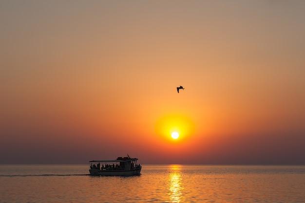 日没時の観光客で日没時のボートは、sc熱の太陽、素晴らしい海の夕日の下で泳ぎます。