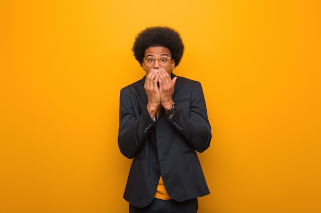 オレンジ色の壁の上の若いビジネスアフリカ系アメリカ人男性は非常にscaと非表示を恐れて