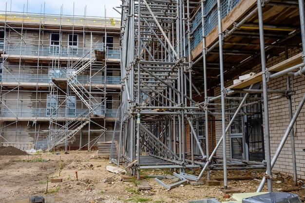 На строительной площадке нового жилого дома вокруг нового многоэтажного дома возведены строительные леса и временная лестница для облицовки, окон и установки крыши