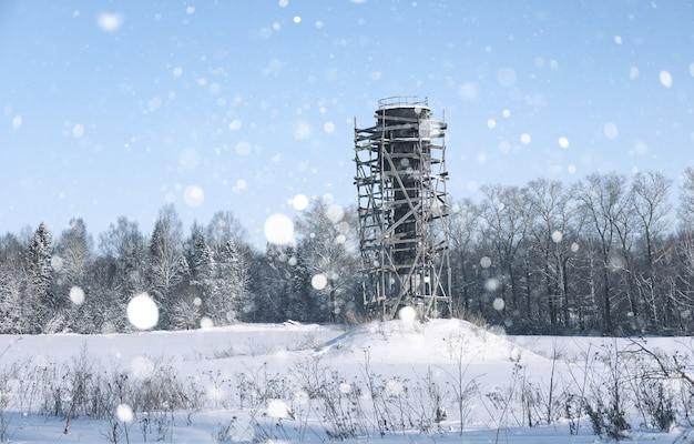 吹雪の中の森の前のフィールドの給水塔の周りの足場