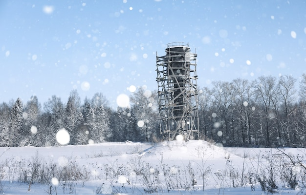 Scaffold around the water tower in the field in front of forest in snow storm