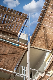 青い空を背景に、木製デッキで足場と足場。高所で工事を行う。建設の安全性。