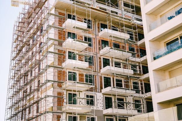 建設中の近代的な高層ビルの周りの足場