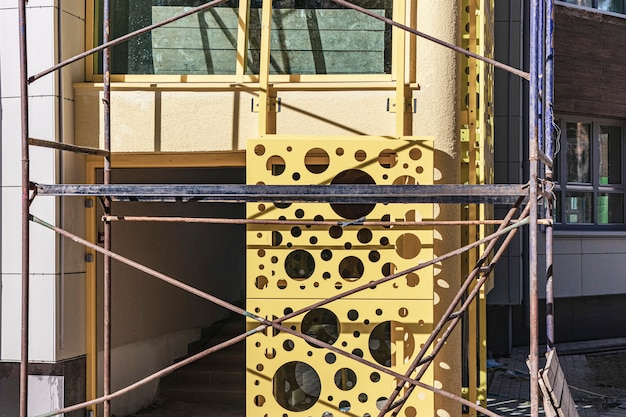 Scaffolding with wooden decks. performing construction work at height. sheathing of the ventilated facade with metal.