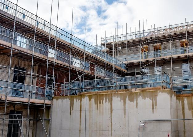 Возведены строительные леса вокруг нового многоэтажного кирпичного дома в новостройке для установки окон и крыши.