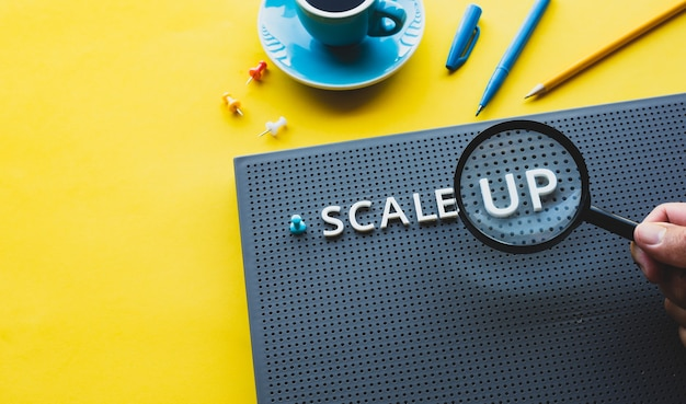 Scale up or startup business concepts with magnifying glass on text performance of investment