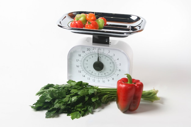 Scale and vegetables, healthy vegetarian food. white background.