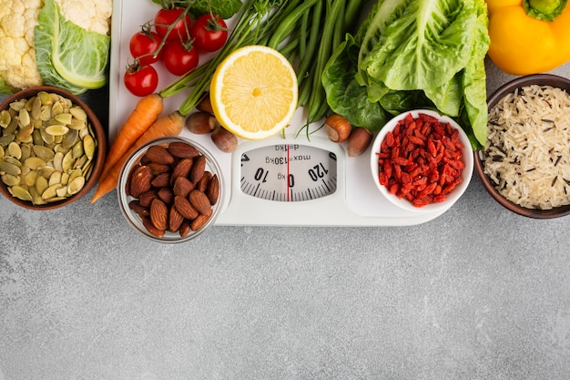 Scale with groceries on gray background