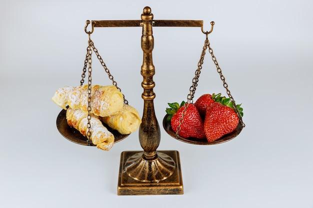 Весы со здоровой и нездоровой пищей на белой поверхности