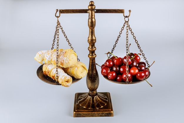 Scale with healthy food and junk food on white surface