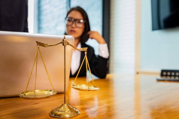 Весы и адвокат работают на ноутбуке.