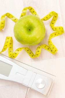 Scales, green apple, measuring tape on a light wooden surface. preparation for the summer season and the beach, weight loss and sports concept. vertical photo