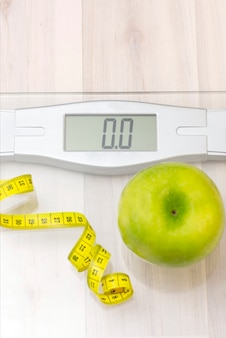 Scales, green apple, measuring tape on a light wooden surface. weight loss and sports concept. vertical photo