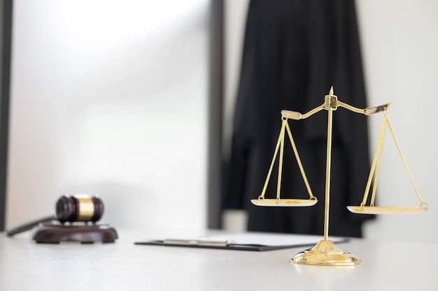 Scales of justice and gavel judge hammer on brown wooden desk with copy space. legislation concept.