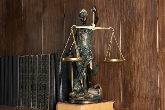 Scales of justice, lady justice, law library concept, law books in the background.