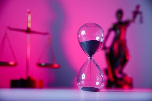 Весы, правосудие и песочные часы в розовом неоне.