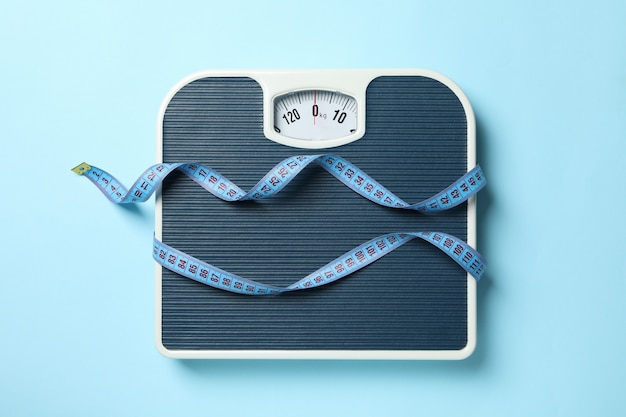 Scales and measuring tape on blue floor. weight loss concept