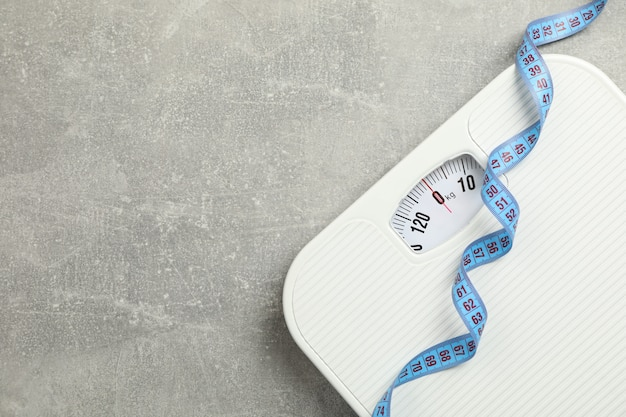 Scales and measuring tape on gray floor. weight loss concept