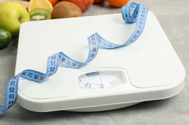 Scales, measuring tape and vegetarian food on gray floor