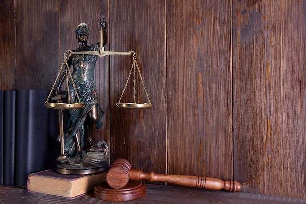 Весы правосудия, леди юстиции, концепция юридической библиотеки, юридические книги в фоновом режиме.