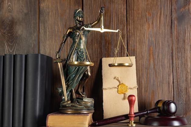 正義のスケール、正義の女神、法律図書館の概念、背景の法律の本。