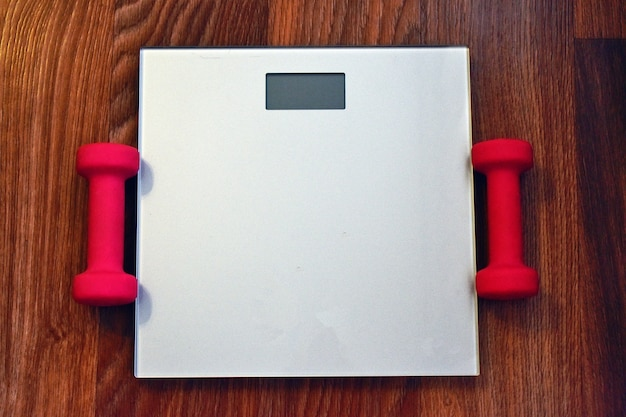 Scales and pink dumbbells in the hall