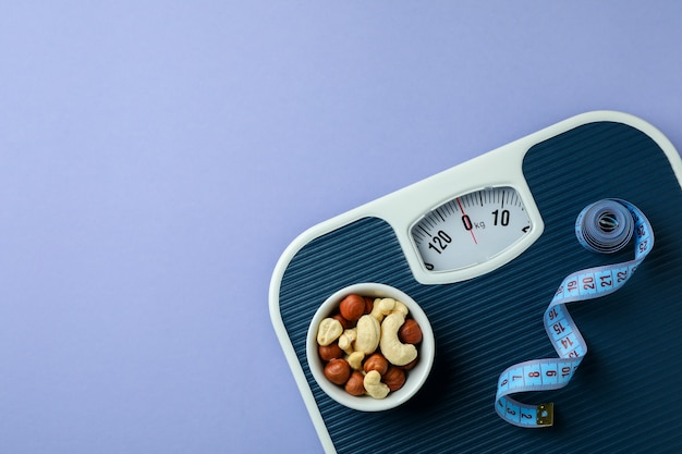 Scales with measuring tape and bowl of nuts isolated
