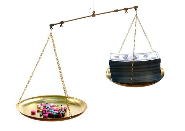 片側に薬、反対側に100米ドルの紙幣が白い表面にあるスケール、高価な治療コンセプト