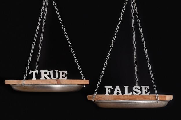 Весы с истиной и ложью. баланс на черной поверхности крупным планом.