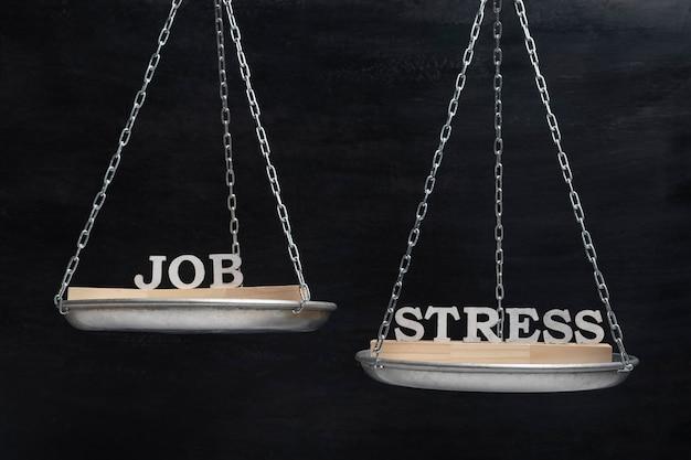 Весы со словами работа и стресс. концепция гармонии. весы на черном фоне крупным планом.