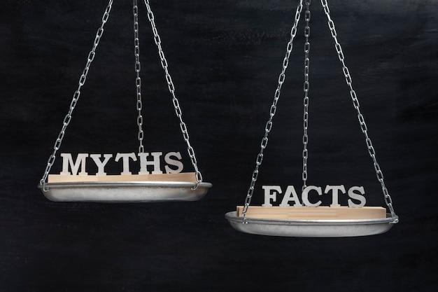 Весы со словами мифы и факты. понятие баланса. весы на черном фоне крупным планом.