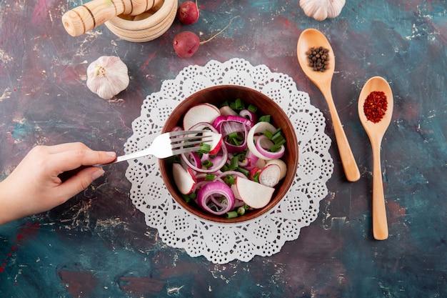 Взгляд сверху руки женщины есть овощной салат с луком редиски и scallion на предпосылке зеленого цвета и maroon