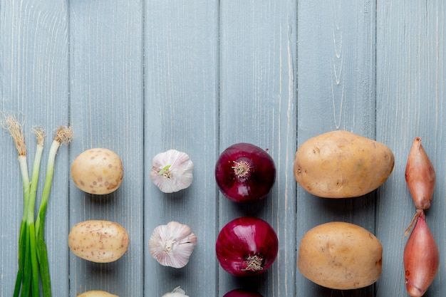Закройте вверх по взгляду картины овощей как лук чеснока картошки scallion на деревянной предпосылке с космосом экземпляра