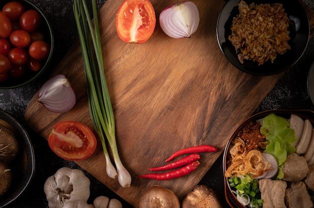 Scalogno, peperoni, aglio e funghi shiitake su un piatto di legno