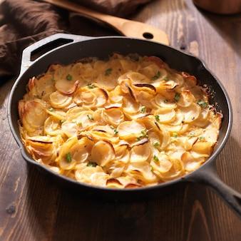 Зубчатый картофель в деревенской железной сковороде