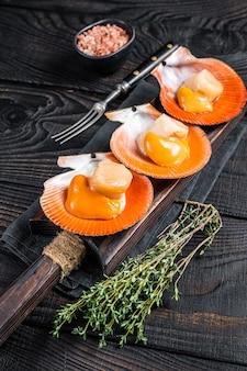 Гребешки сырые моллюски на деревянной доске с травами. черный деревянный фон. вид сверху.